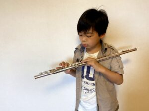 初めてのフルートを持ってみた小学6年生の男の子の画像です