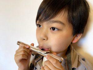 フルートの頭部管での練習をしている少年の画像