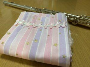 フルートマットを畳んだ状態をアップにした画像なので、飾りとピンクの袋状の生地の柄がよく分かります。